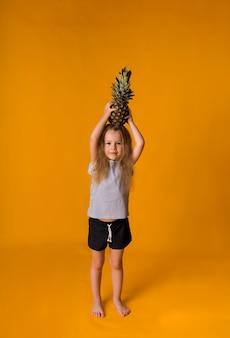 Szczęśliwa mała blondynka trzyma ananasa na głowie na żółtej powierzchni z kopią miejsca