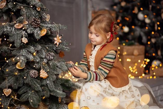 Szczęśliwa mała blondynka w świątecznych ubraniach, dekorująca choinkę i uśmiechnięta, przygotowująca się do świątecznych świąt i nowego roku.