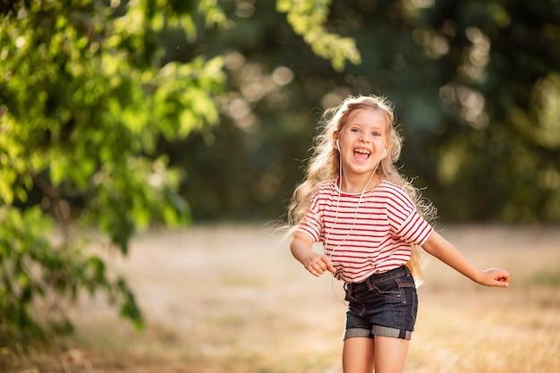 Szczęśliwa mała blondynki dziewczyna słucha muzyka z hełmofonami, tanczy i śpiewa w naturze w parku.