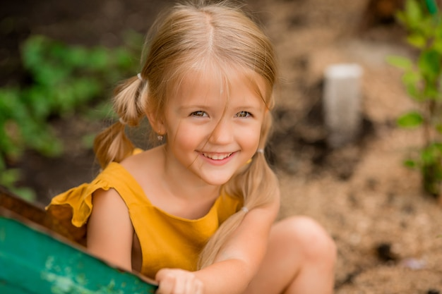 Szczęśliwa mała blondynki dziewczyna w kraju w ogrodowym taczki obsiadaniu ono uśmiecha się