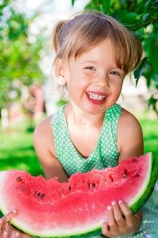 Szczęśliwa mała blondynki dziewczyna z dużym plasterka arbuzem w lato czasie w parku, plenerowym.