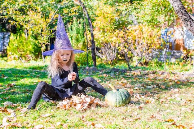 Szczęśliwa mała czarownica baw się na zewnątrz w halloween. cukierek albo psikus.