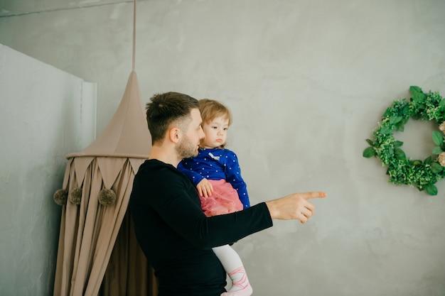 Szczęśliwa mała dzieciak dziewczyna cieszy się słodkiego moment z tata w żywym pokoju