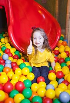 Szczęśliwa mała dziewczynka bawi się i bawi się w przedszkolu z kolorowymi kulkami i pokazuje kciuk w górę w centrum zabaw