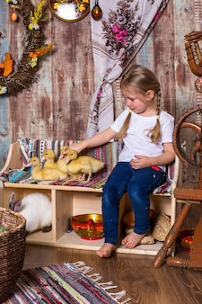 Szczęśliwa mała dziewczynka bawi się słodkimi puszystymi kaczuszkami wielkanocnymi