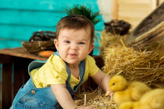 Szczęśliwa mała dziewczynka bawi się uroczymi puszystymi wielkanocnymi kaczuszkami.