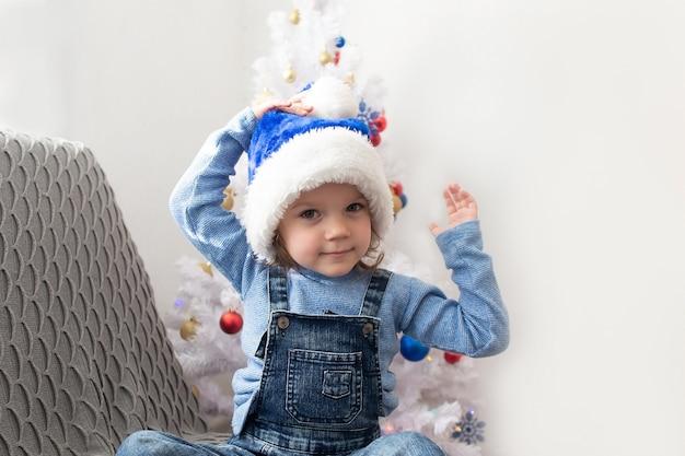 Szczęśliwa mała dziewczynka bawi się w domu w boże narodzenie