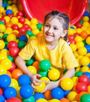 Szczęśliwa mała dziewczynka bawić się w kolorowe kulki. szczęśliwe dziecko grając w kolorowe plastikowe kulki w centrum zabaw