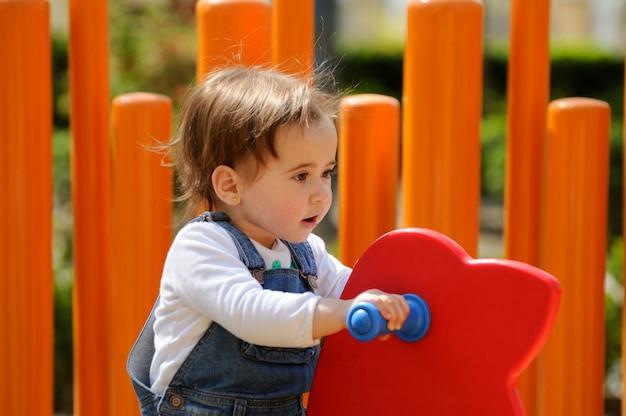 Szczęśliwa mała dziewczynka bawić się w miastowym boisku.