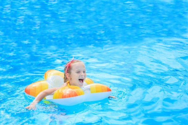 Szczęśliwa mała dziewczynka bawić się z kolorowym nadmuchiwanym pierścionkiem w plenerowym pływackim basenie w gorącym letnim dniu. dzieci uczą się pływać. zabawki wodne dla dzieci. dzieci bawią się w tropikalnym kurorcie. rodzinne wakacje na plaży.