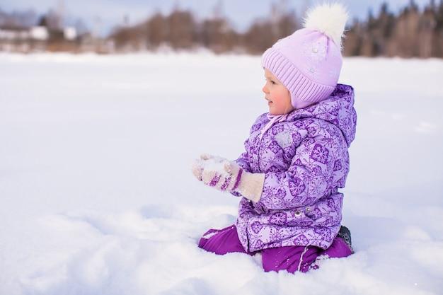 Szczęśliwa mała dziewczynka bawić się z śniegiem przy zima słonecznym dniem