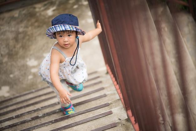 Szczęśliwa mała dziewczynka chodzi w górę schodków. kid first step concept.