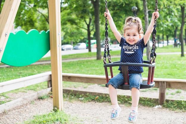 Szczęśliwa mała dziewczynka cieszy się w huśtawce