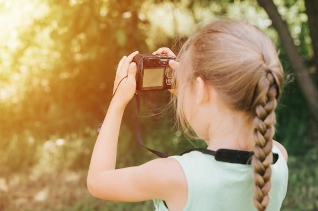 Szczęśliwa Mała Dziewczynka Fotografuje Letni Naturalny Krajobraz Za Pomocą Aparatu, Korzystając Z Podglądu Na żywo Premium Zdjęcia