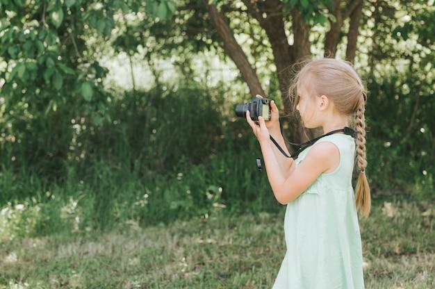 Szczęśliwa mała dziewczynka fotografuje letni naturalny krajobraz za pomocą aparatu, korzystając z podglądu na żywo