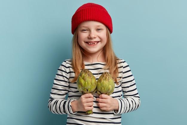 Szczęśliwa mała dziewczynka gospodarstwa karczochów