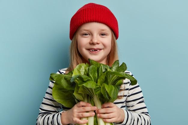 Szczęśliwa mała dziewczynka gospodarstwa sałatki