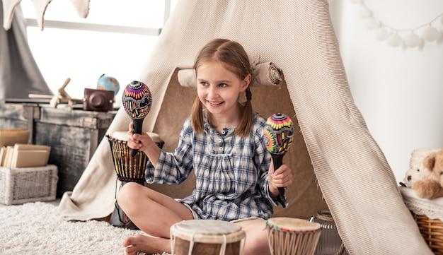 Szczęśliwa mała dziewczynka gra na marakasach