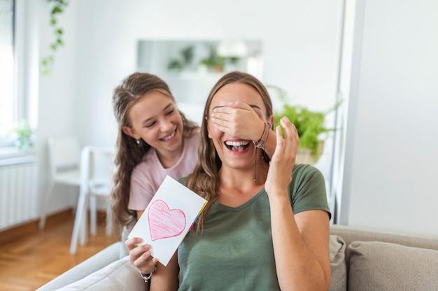 Szczęśliwa mała dziewczynka gratuluje uśmiechniętej mamie i daje kartkę z czerwonym sercem podczas świętowania w domu, zasłaniając oczy i zaskakując ją