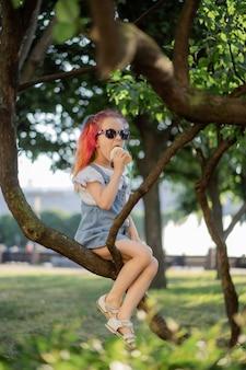 Szczęśliwa mała dziewczynka jedząca lody na gałęzi drzewa