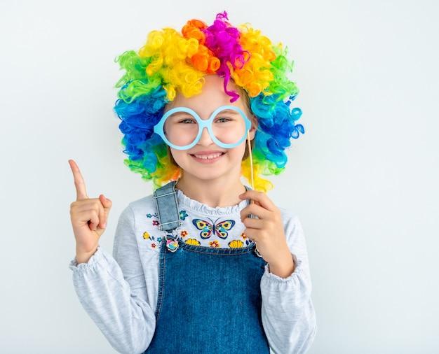 Szczęśliwa mała dziewczynka jest ubranym błazen perukę