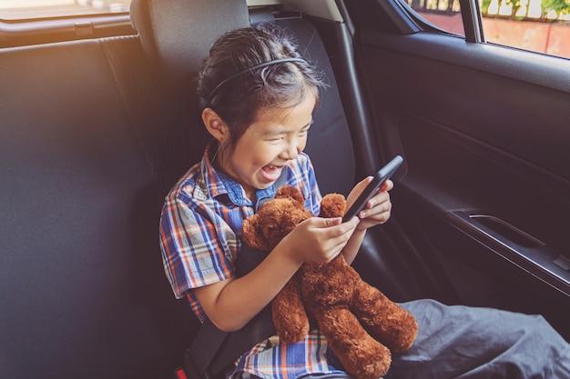 Szczęśliwa mała dziewczynka jest ubranym pasy bezpieczeństwa w samochodzie