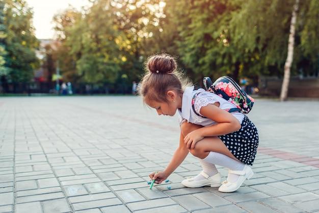 Szczęśliwa mała dziewczynka jest ubranym plecaka i rysuje z kredą outdoors szkołą podstawową. dzieciak bawi się po zajęciach