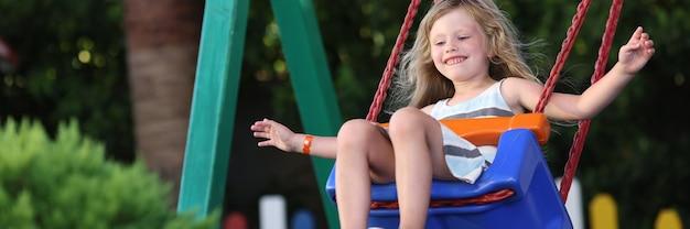Szczęśliwa mała dziewczynka kołysząca się na koncepcji huśtawki
