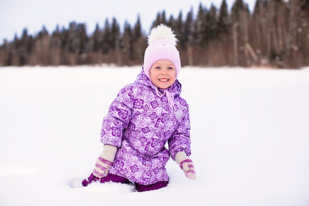 Szczęśliwa mała dziewczynka ma zabawę na śniegu przy zima słonecznym dniem
