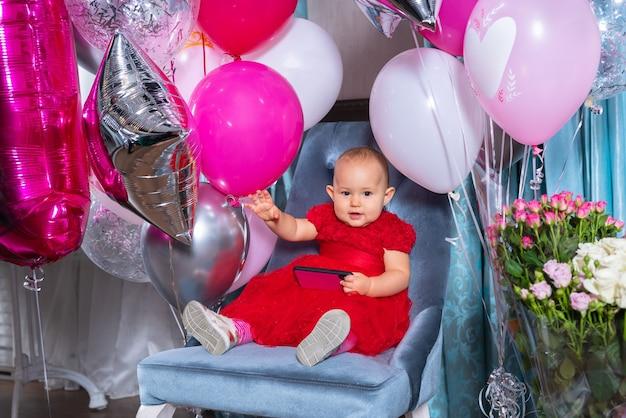 Szczęśliwa mała dziewczynka macha, świętując swoje pierwsze urodziny w pozycji siedzącej