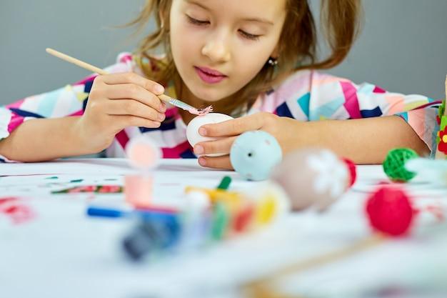 Szczęśliwa mała dziewczynka malowanie, rysowanie pędzlem jaj w domu. dziecko przygotowuje się do wielkanocy, bawiąc się i obchodzi święto. wesołych świąt wielkanocnych