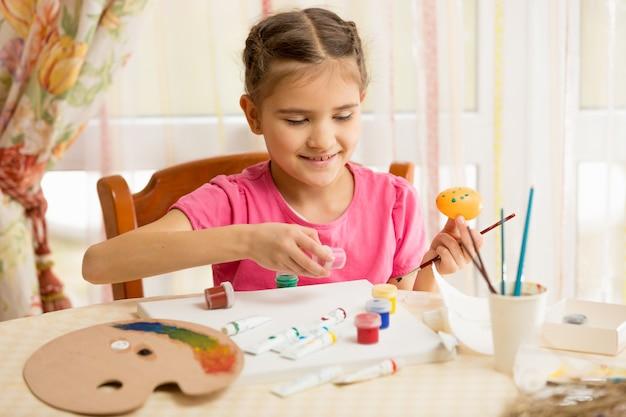 Szczęśliwa mała dziewczynka maluje jajka na wielkanoc