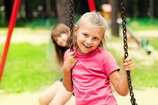 Szczęśliwa mała dziewczynka na huśtawce
