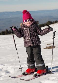 Szczęśliwa mała dziewczynka na nartach zjazdowych