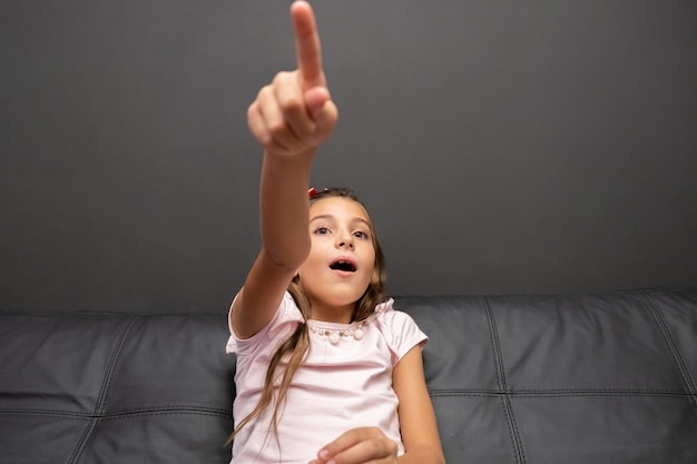 Szczęśliwa mała dziewczynka ogląda tv w nocy obsiadaniu na leżance w żywym pokoju w domu