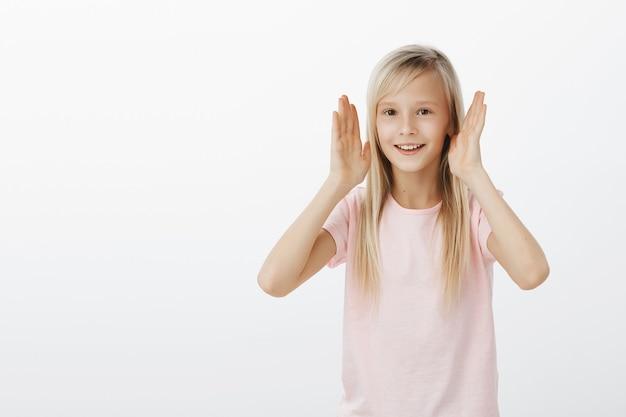 Szczęśliwa mała dziewczynka otwiera oczy i wygląda na zaskoczoną
