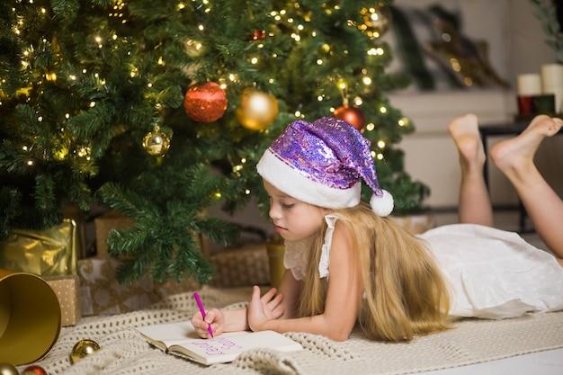 Szczęśliwa mała dziewczynka pisze list do świętego mikołaja w urządzonym pokoju bożonarodzeniowym