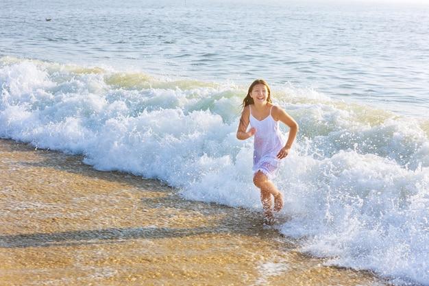 Szczęśliwa mała dziewczynka pływająca w wodzie dziewczyna na plaży bawi się w oceanie