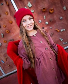 Szczęśliwa mała dziewczynka pozuje obok ściany wspinaczkowej