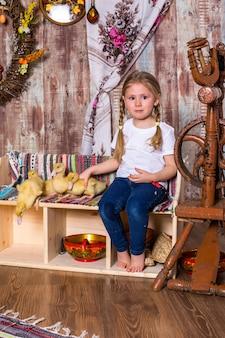 Szczęśliwa mała dziewczynka pozuje z uroczymi puszystymi kaczuszkami wielkanocnymi
