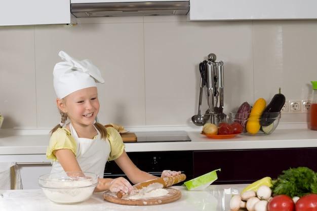 Szczęśliwa mała dziewczynka robi pizzę w kuchni