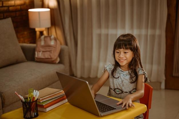 Szczęśliwa mała dziewczynka robi pracie domowej używać laptop