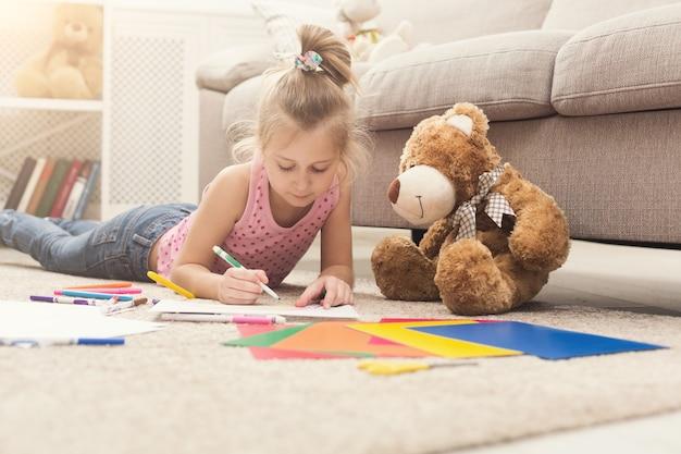 Szczęśliwa mała dziewczynka rysunek. słodkie dziecko leżące w domu na podłodze wśród kolorowego papieru i ołówków. diy, kreatywne hobby artystyczne, koncepcja wczesnego rozwoju i inspiracji