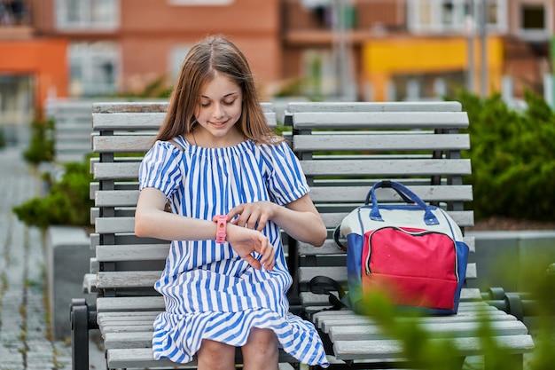 Szczęśliwa mała dziewczynka siedzi i używa swojego inteligentnego zegarka dla dzieci w pobliżu szkoły.