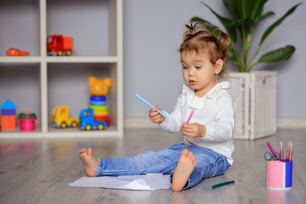 Szczęśliwa mała dziewczynka siedzi na podłodze i rysuje na papierze kredkami