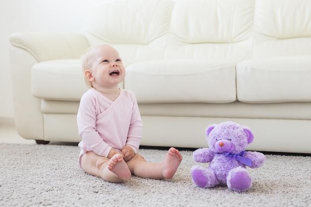 Szczęśliwa mała dziewczynka siedzi na podłodze w domu