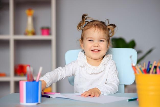 Szczęśliwa mała dziewczynka siedzi przy stole i rysuje na papierze kredkami
