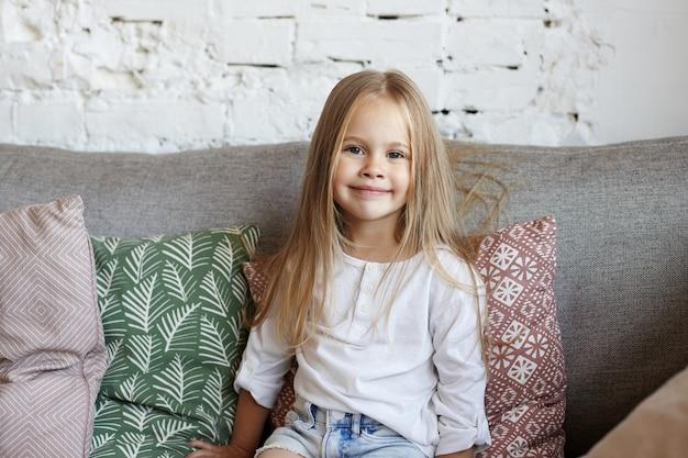 Szczęśliwa mała dziewczynka siedzi w salonie
