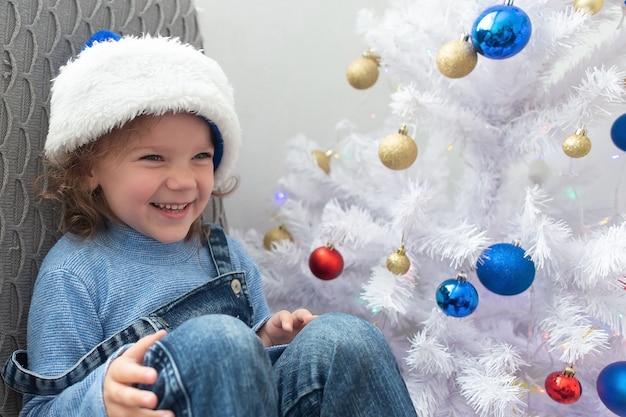 Szczęśliwa mała dziewczynka śmieje się w domu na boże narodzenie
