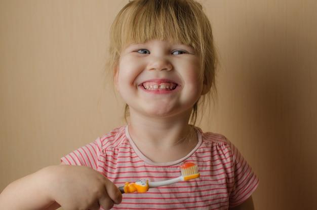 Szczęśliwa mała dziewczynka szczotkuje jej zęby. skopiuj miejsce
